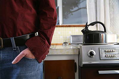 Man standing in kitchen - p4340157f by Mike Hipple