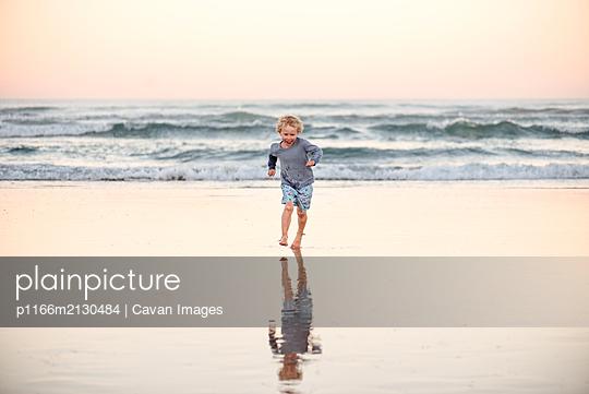 Happy little boy running on beach - p1166m2130484 by Cavan Images