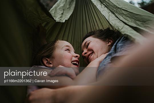 Siblings hugging and smiling in hammock outside - p1166m2201362 by Cavan Images