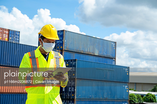 Young worker man with digital tablet at container terminal port, - p1166m2236872 by Cavan Images