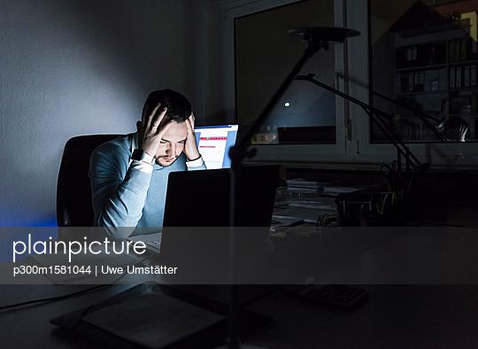 Tired businessman sitting at desk in office at night - p300m1581044 von Uwe Umstätter