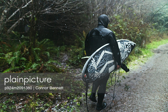 Young male surfer in wetsuit walking along puddled dirt track in rain, rear view, Arcata, California, United States - p924m2091380 by Connor Bennett
