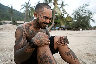 hipster guy with tattoo sitting on the beach in thailand - p1166m2269088 by Cavan Images