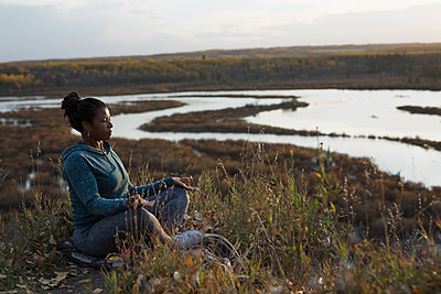 Serene woman meditating in lotus position on autumn hillside overlooking lake - p1192m1194126 by Hero Images