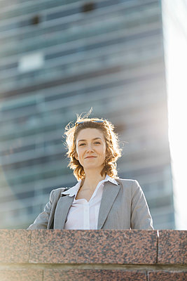 Successful young businesswoman standing at wall in front of office building - p300m2104000 by Josep Rovirosa