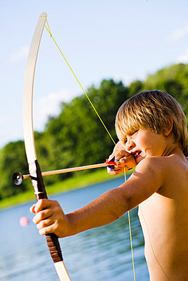 Shirtless boy aiming bow and arrow - p312m695526 by Plattform photography