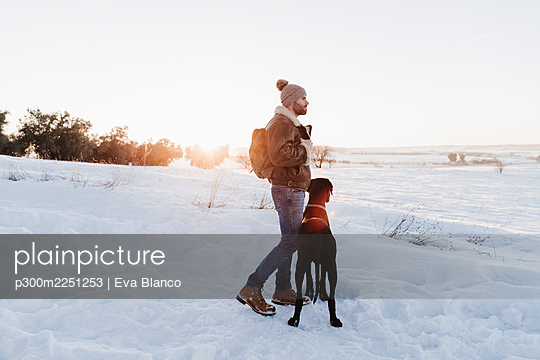 Male backpacker standing with Great Dane dog while looking away in snow - p300m2251253 by Eva Blanco