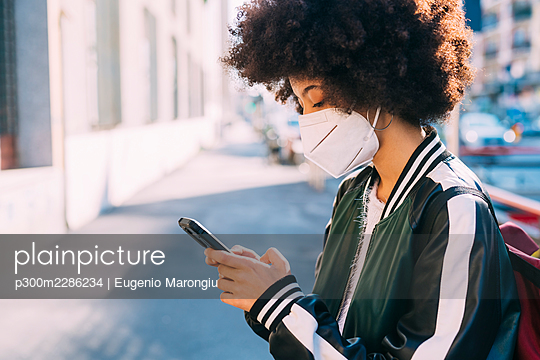 Young multiethnic woman wearing mask using smartphone outdoor - Italy; Lombardy; Milan - p300m2286234 von Eugenio Marongiu