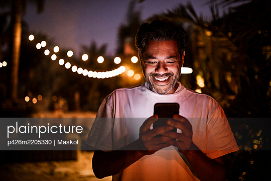 Happy man texting during sunset - p426m2205330 by Maskot