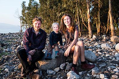Junge Familie an einem Steinstrand - p1046m1138225 von Moritz Küstner