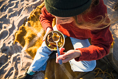 Young woman enjoying soup while beach car camping alone - p1166m2285575 by Cavan Images