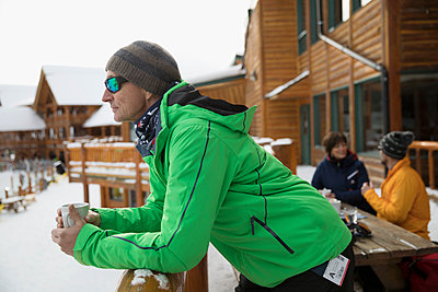 Thoughtful male skier enjoying coffee on snowy ski resort balcony - p1192m1546511 by Hero Images