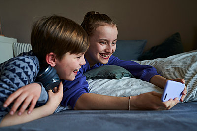 Laughing sibblings lying together on bed using smartphone for video chat - p300m2180174 by Stefanie Aumiller