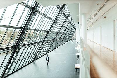 Businessman walking in office corridor - p300m2265678 by Gustafsson