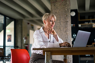 Smiling businesswoman holding eyeglasses while using laptop at desk by column at home office - p300m2267797 by Robijn Page