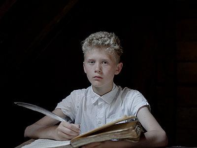 Boy with blond hair doing his homework - p945m1154601 by aurelia frey
