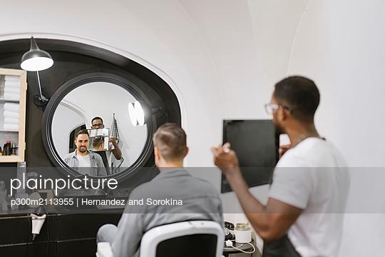 Barber showing man his haircut in mirror at barber shop - p300m2113955 von Hernandez and Sorokina