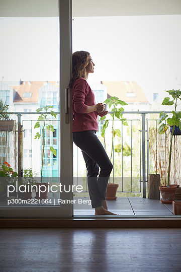 Woman drinking coffee while standing by balcony at home - p300m2221664 by Rainer Berg