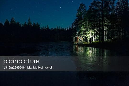Small wooden cabin at lakeshore at night - p312m2285506 by Matilda Holmqvist