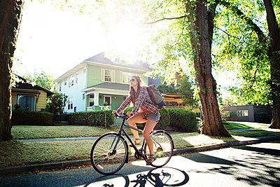 Full length of woman riding bicycle on street during summer - p1166m1163699 by Cavan Images