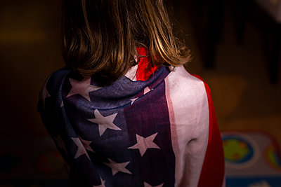 6-year-old anonymous girl wrapped in the American flag - p1166m2193966 by Cavan Images
