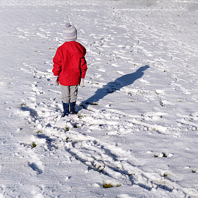 Little boy alone in a snow covered field - p1228m1511436 by Benjamin Harte