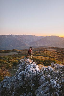 Man on rock by mountains at sunset - p1427m2163673 by Oleksii Karamanov