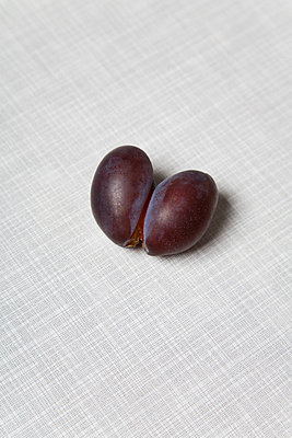 Two plums on a table - p2380294 by Anja Bäcker