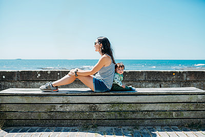 France, mother and baby girl sitting back to back on a bench at beach promenade - p300m2004742 von Gemma Ferrando