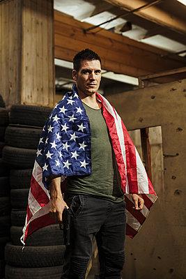 Portrait of man wearing American flag holding a gun - p300m2062119 by Kike Arnaiz