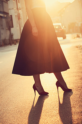 Low section view of woman wearing skirt and high heels standing on street on sunset - p577m1589708 by Mihaela Ninic