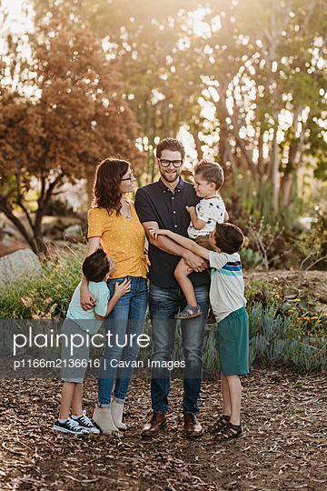 Portrait of family smiling at each other and hugging in cactus garden - p1166m2136616 by Cavan Images