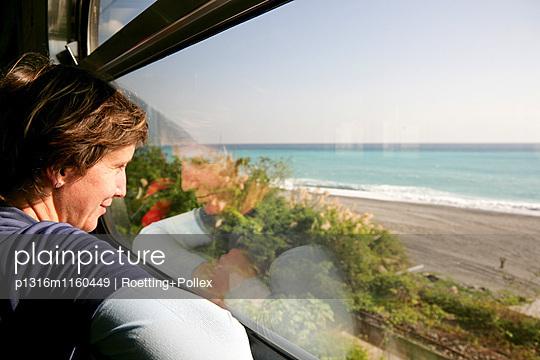 Junge deutsche Frau im Zug am Fenster, Blick auf Meer und Strand, Hualien, Republik China, Taiwan, Asien - p1316m1160449 von Roetting+Pollex