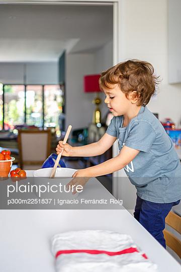 Cute boy cooking in kitchen at home - p300m2251837 by Ignacio Ferrándiz Roig