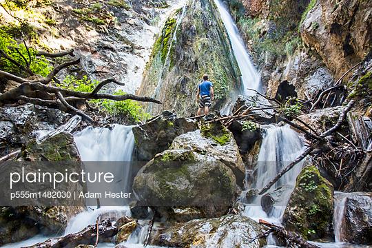 Caucasian man standing on rocks watching waterfall - p555m1482030 by Adam Hester