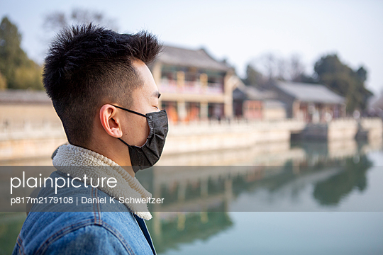 Profile of young man with community mask - p817m2179108 by Daniel K Schweitzer
