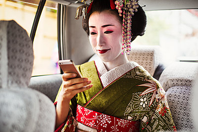A woman dressed in the traditional geisha style, wearing a kimono and obi, with an elaborate hairstyle and floral hair clips, with white face makeup with bright red lips and dark eyes in a car using a smart phone.  - p1100m1185728 by Mint Images
