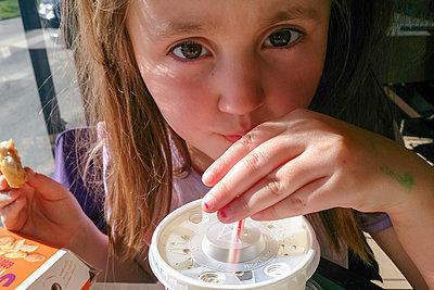Little girl eating burger and drinking soda - p1418m2004851 by Jan Håkan Dahlström