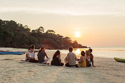 Thailand, Koh Phangan, group of people sitting on a beach with guitar at sunset - p300m1568329 by Mosuno Media