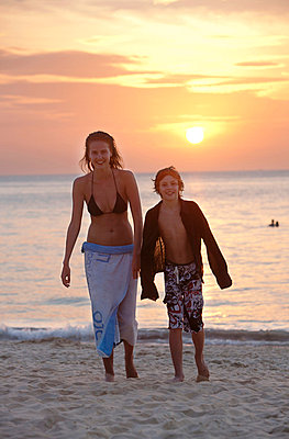 Boy and girl walking on beach at sunset - p31228422 by Per Eriksson