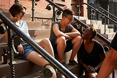 Friends relaxing on front stoop - p555m1409842 by Granger Wootz