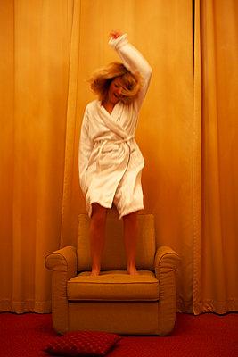 Frau in Bademantel hüpft auf Sessel herum - p795m2087466 von JanJasperKlein