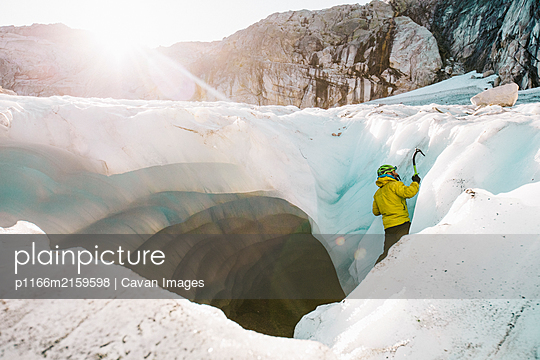 Side view of man ice climbing outside of glacial cave. - p1166m2159598 by Cavan Images