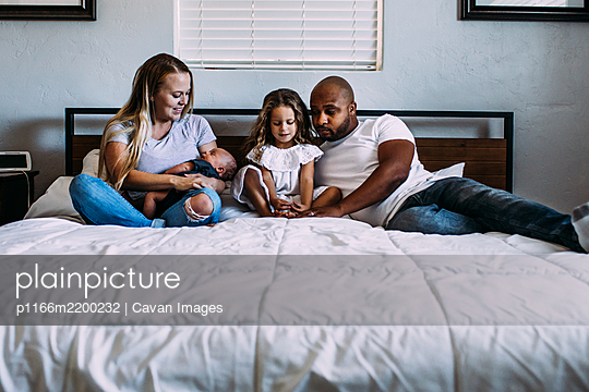 A family snuggling on the bed with newborn baby - p1166m2200232 by Cavan Images