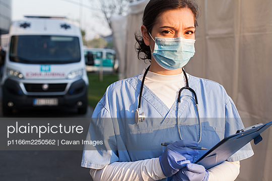 Worried & anxious UK NHS EMS doctor holding patient report form folder - p1166m2250562 by Cavan Images