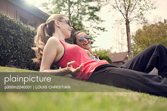 Exhausted female friends smiling while relaxing on grass in suburb - p300m2240001 by LOUIS CHRISTIAN