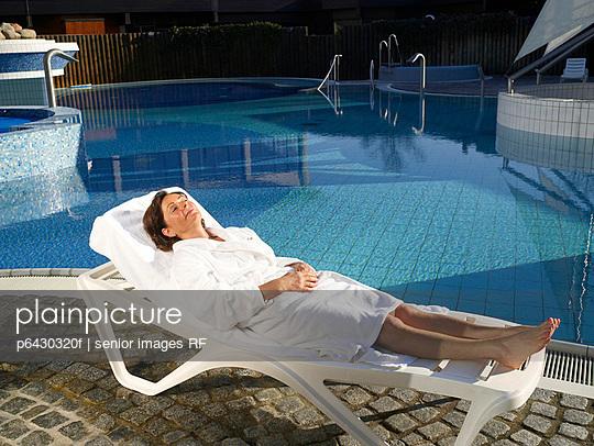Aeltere Frau in weissem Bademantel am Pool  - p6430320f von senior images RF