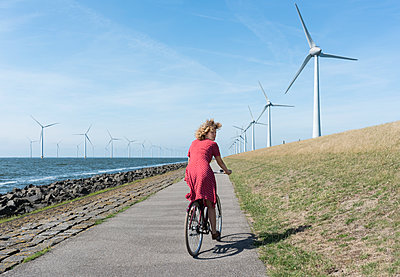 Girl cycling along windfarm - p1132m1591231 by Mischa Keijser
