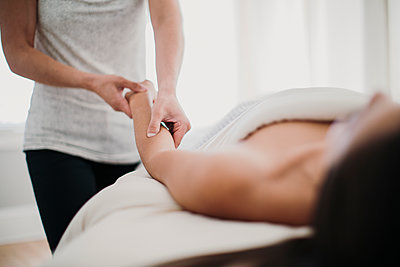 A woman gets a massage from a therapist in a relaxing environment - p1166m2107018 by Cavan Images