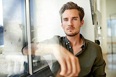 Portrait of serious young man sitting behind windowpane - p300m2059578 von Philipp Nemenz
